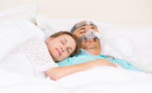 Man with sleeping apnea and CPAP machine asleep in bed